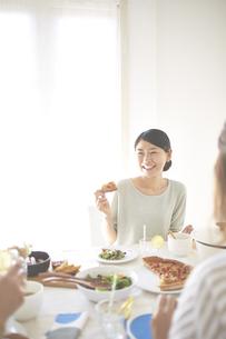会話を楽しみながらピザを食べる女性の素材 [FYI01034193]
