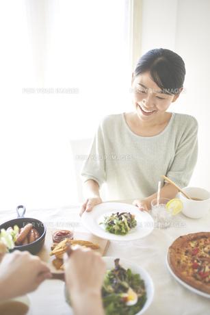 ランチのサラダを取り分けてもらっている女性の素材 [FYI01034209]