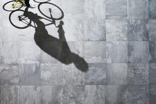 光が差し込む石の床を自転車で走る男性の素材 [FYI01034215]