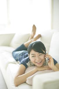ソファーの上で電話している女性の素材 [FYI01034218]