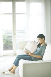 ソファーに座りながら読書している女性の素材 [FYI01034225]