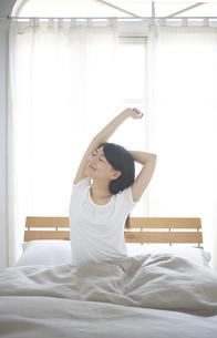ベッドの上でストレッチをする女性の素材 [FYI01034228]