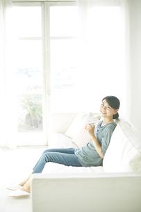 ソファーに座りながら飲み物を飲んでいる女性の素材 [FYI01034259]