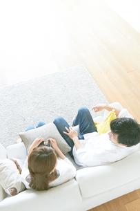 ソファで本を読む夫婦と茶色の木の床の素材 [FYI01034267]