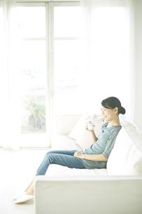 ソファーに座りながら飲み物を飲んでいる女性の素材 [FYI01034268]