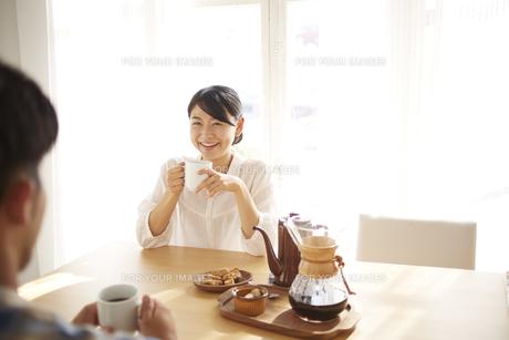 男性とコーヒーを飲みながら会話している女性の素材 [FYI01034282]