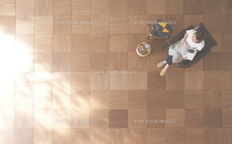 茶色の木の床とソファに座る女性の素材 [FYI01034285]