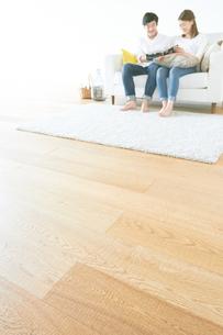 ソファで本を読む夫婦と茶色の木の床の素材 [FYI01034298]