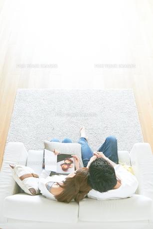 ソファで本を読む夫婦と茶色の木の床の素材 [FYI01034322]