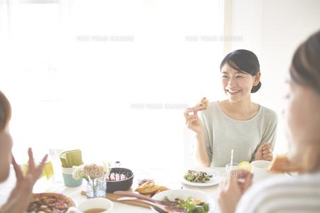 会話を楽しみながらピザを食べる女性の素材 [FYI01034346]