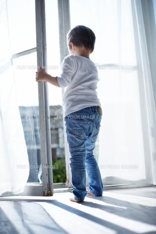 窓の外に出ようとしている男の子の素材 [FYI01034501]