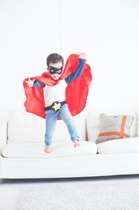 ソファーからジャンプするちびっこスーパーマンの素材 [FYI01034533]