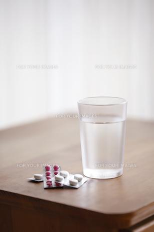 木の机の上のグラスと錠剤の薬の素材 [FYI01044057]