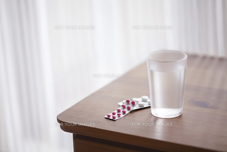 カーテン越しに日差しが入る机の上のグラスと錠剤の薬の素材 [FYI01044065]
