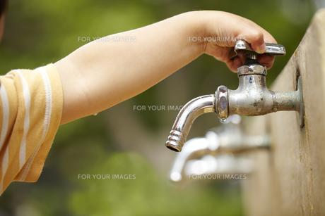 水道の蛇口の栓を閉める子供の手の素材 [FYI01044084]