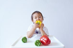 ベビーチェアーに座ってパプリカを食べる幼児の素材 [FYI01044089]