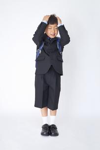 スーツで青いランドセルを背負い頭をかかえる小学一年生の素材 [FYI01044096]