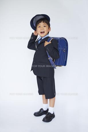 スーツで青いランドセルを背負い帽子を脱ぐ小学一年生の素材 [FYI01044103]