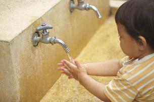 外の水道で手を洗う子供の素材 [FYI01044130]