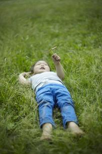 竹とんぼを持って草むらに寝転ぶ子供の素材 [FYI01044153]