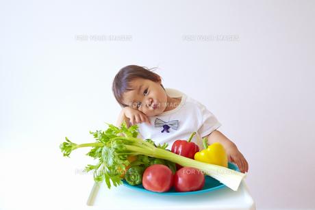 セロリやトマト、ピーマン、パプリカなどの野菜の前で考える幼児の素材 [FYI01044160]