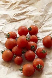 ベージュ色の包装紙の上に置いた有機野菜のミニトマトの素材 [FYI01044196]