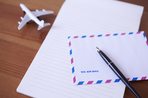 飛行機の模型が置かれた木の机の上のエアメールと万年筆の素材 [FYI01044209]