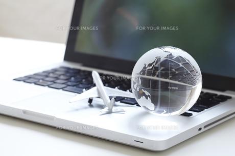 ノートブックの上に地球儀と飛行機の模型の素材 [FYI01044211]