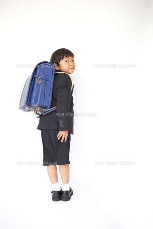 スーツで青いランドセルを背負い振り向く小学一年生の素材 [FYI01044217]