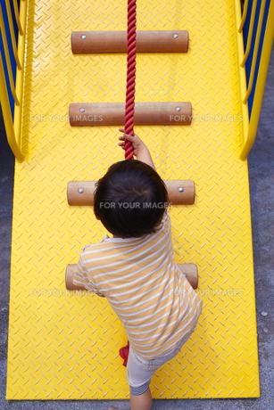 アスレチックの遊具をロープで登る子供の素材 [FYI01044242]