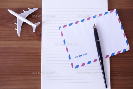 飛行機の模型が置かれた木の机の上のエアメールと万年筆の素材 [FYI01044269]