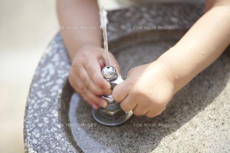 公園の飲み水の蛇口を開ける子供の手の素材 [FYI01044276]