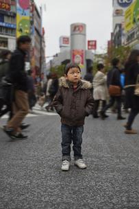 東京渋谷スクランブル交差点に悲しい顔をして佇む子供の素材 [FYI01044290]