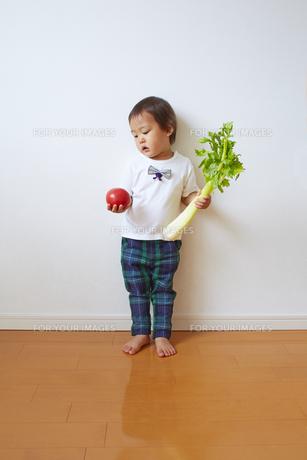 トマトとセロリを持って立っている幼児の素材 [FYI01044292]