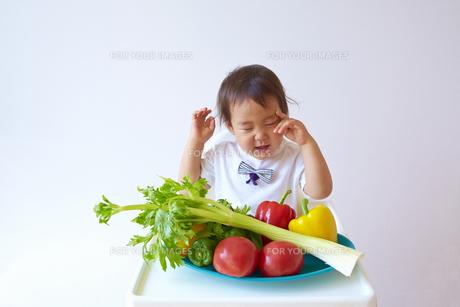 セロリやトマト、ピーマン、パプリカなどの野菜の前で泣く幼児の素材 [FYI01044320]