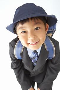 スーツで青いランドセルを背負い前かがみになる小学一年生の素材 [FYI01044337]