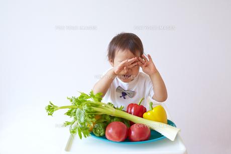 セロリやトマト、ピーマン、パプリカなどの野菜の前で泣く幼児の素材 [FYI01044344]
