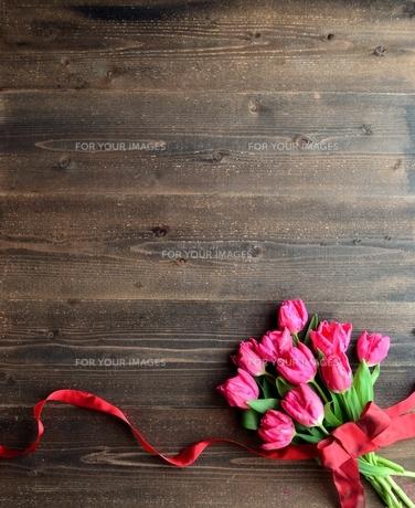 ピンクのチューリップの花束 黒木材背景の写真素材 [FYI01052258]