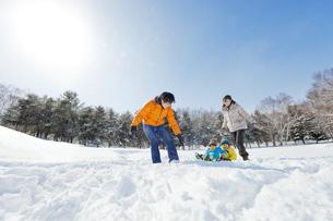 雪の公園でソリを引いて歩く親子の素材 [FYI01074971]