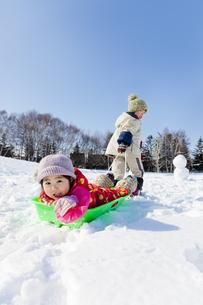 雪の公園でソリを引いて遊ぶ子供たちの素材 [FYI01075035]