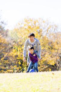 秋の公園でボール遊びをする息子と父親の素材 [FYI01075061]
