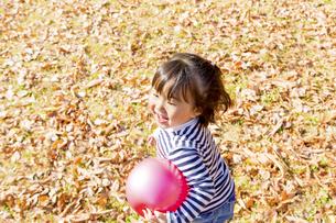 秋の公園でボール遊びをする女の子の素材 [FYI01075085]
