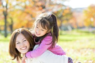 秋の公園で母親に抱きつく女の子の素材 [FYI01075113]