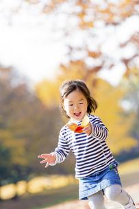 秋の公園を落葉を持って走る女の子の素材 [FYI01075148]