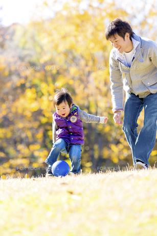 秋の公園でボール遊びをする息子と父親の素材 [FYI01075172]