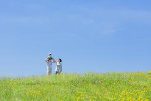 野花の咲く丘で遊ぶ親子の素材 [FYI01075186]