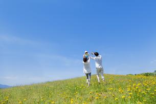 野花の咲く丘で遊ぶ親子の素材 [FYI01075204]