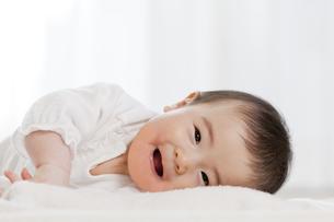 リビングで横になって笑う赤ちゃんの素材 [FYI01075247]