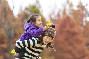 秋の公園で妹をおんぶする姉の素材 [FYI01075258]