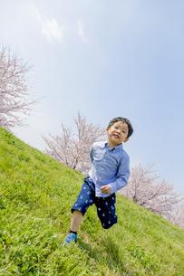 桜の咲く土手で遊ぶ男の子の素材 [FYI01075266]